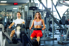 Атлетический человек и женщина делая разминку на имитаторе rowing в cros Стоковая Фотография RF