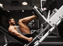 Атлетический человек культуризма в ноге спортзала Стоковые Изображения RF