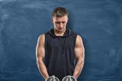 Атлетический человек стоит с сжатиями в его руках и классн классном за им Стоковые Изображения