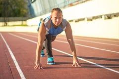 Атлетический человек стоя в позиции готовой для того чтобы побежать дальше Стоковые Фотографии RF