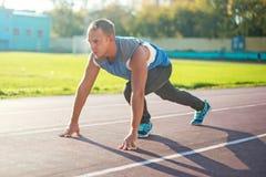 Атлетический человек стоя в позиции готовой для того чтобы побежать на третбане Стоковые Фото