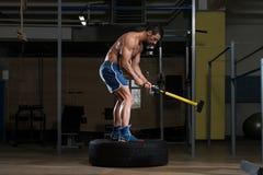 Атлетический человек ударяет автошину Стоковое фото RF
