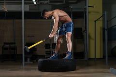 Атлетический человек ударяет автошину Стоковое Изображение RF