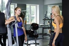 2 атлетических белокурых женщины говоря в спортзале Девушка связывает с тренером Стоковые Изображения
