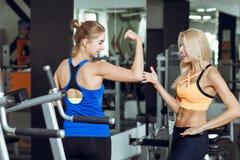 2 атлетических белокурых женщины говоря в спортзале Девушка связывает с тренером Стоковая Фотография