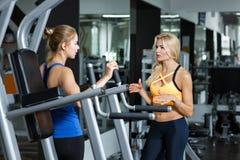 2 атлетических белокурых женщины говоря в спортзале Девушка связывает с тренером Стоковые Фотографии RF