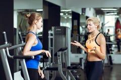 2 атлетических белокурых женщины говоря в спортзале Девушка связывает с тренером Стоковые Изображения RF