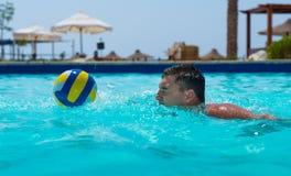 Атлетическое заплывание человека и пробовать уловить шарик в бассейне Стоковые Фото