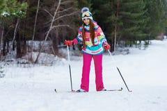 Атлетическое катание на лыжах девушки в ярких одеждах Стоковая Фотография