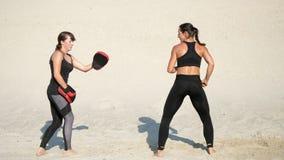 2 атлетическое, молодые женщины в черных костюмах фитнеса принимансяы за пара, разрабатывают пинки, на дезертированном пляже, про видеоматериал