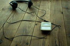 Аудиоплейер и наушники на деревянной предпосылке Стоковые Фотографии RF