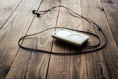 Аудиоплейер и наушники на деревянной предпосылке Стоковые Изображения RF
