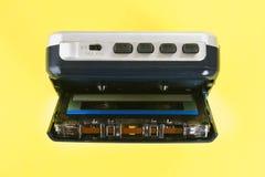 Аудиоплейер кассеты с кассетой и наушниками на желтой пастельной предпосылке Стоковые Изображения RF