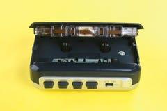 Аудиоплейер кассеты с кассетой и наушниками на желтой пастельной предпосылке Стоковое фото RF