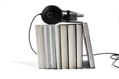 Аудио концепция книги Большие черные наушники на стоге книг на белой предпосылке r стоковые фотографии rf