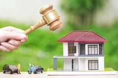 Аукцион свойства, рука женщины дом молотка удерживания деревянный и модельный на естественной зеленой предпосылке, юристе домашне стоковые изображения