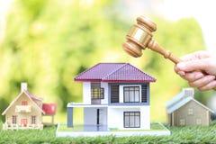 Аукцион свойства, рука женщины дом молотка удерживания деревянный и модельный на естественной зеленой предпосылке, юристе домашне стоковое фото rf