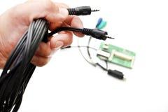 Аудио шнур в руке на белой предпосылке стоковое изображение rf