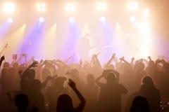 Аудитория на концерте с оружиями подняла в силуэте стоковые изображения