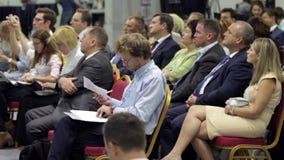 Аудитория представления бизнес-конференции слушает видеоматериал