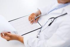 ауmaledoktorn studerar kardiogrammet royaltyfri foto