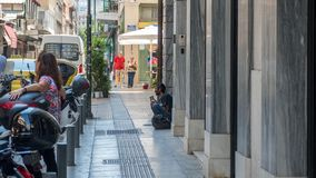 Афины Греция 17-ое августа 2018: Бездомный человек сидя на шаге на s стоковое изображение rf