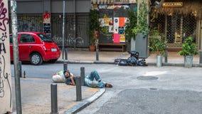 Афины Греция 17-ое августа 2018: Бездомный человек спать на stre стоковые изображения rf