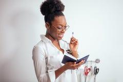 Африканская белошвейка девушки делая примечания на тетради дизайнерские эскизы чертежа Стоковое Изображение