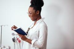 Африканская белошвейка девушки делая примечания на тетради дизайнерские эскизы чертежа Стоковые Изображения RF