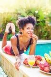 Африканская девушка есть плодоовощ около бассейна Стоковое Изображение RF