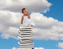 Африканская девушка сидя на высоком стоге книг стоковые фото