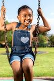 Африканская девушка сидя на качании в парке Стоковое фото RF