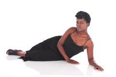 Африканская женщина в черном платье кладя вниз Стоковое Изображение