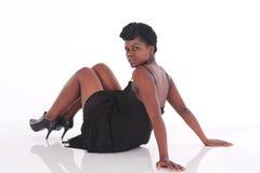 Африканская женщина в черном платье кладя вниз Стоковые Изображения