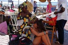Африканская женщина делая оплетки в бортовой прогулке рядом с пляжем к молодому женскому туристу стоковые изображения