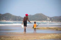 Африканская женщина и ребенок идя на пляж Стоковые Изображения