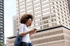 Африканская женщина идя вниз с улицы и слушая к музыке Стоковые Фотографии RF