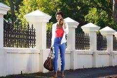 Африканская женщина идя и говоря на мобильном телефоне Стоковая Фотография