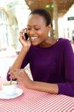 Африканская женщина на кафе имея кофе и говоря на мобильном телефоне Стоковое Фото