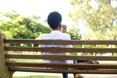 Африканская женщина сидя на скамейке в парке используя сотовый телефон Стоковое Изображение