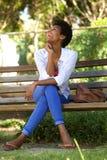 Африканская женщина смеясь над на скамейке в парке Стоковое Фото