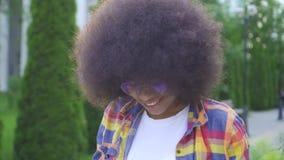 Африканская женщина с афро фотографом стиля причесок с камерой на городском ландшафте смотря камеру и усмехаться акции видеоматериалы