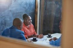 Африканская коммерсантка говоря к коллегам на столе офиса Стоковое Изображение RF