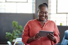 Африканская коммерсантка работая с цифровой таблеткой в офисе Стоковые Изображения RF