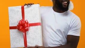 Африканская футболка молодого человека белая держа большую подарочную коробку, продажу рождества, праздненство акции видеоматериалы