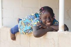 Африканская черная девушка усмехаясь и смеясь над Outdoors космосом экземпляра Стоковые Изображения RF