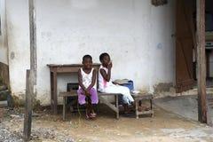Африканские девушки сидят перед домом Стоковые Изображения