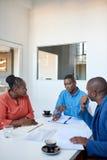 Африканские коллеги дела обсуждая обработку документов в офисе Стоковые Изображения RF