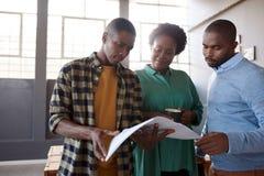 Африканские коллеги работы обсуждая обработку документов совместно в современном офисе Стоковая Фотография