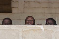 Африканские мальчики и девушки имея потеху Outdoors смеясь над Стоковые Фотографии RF